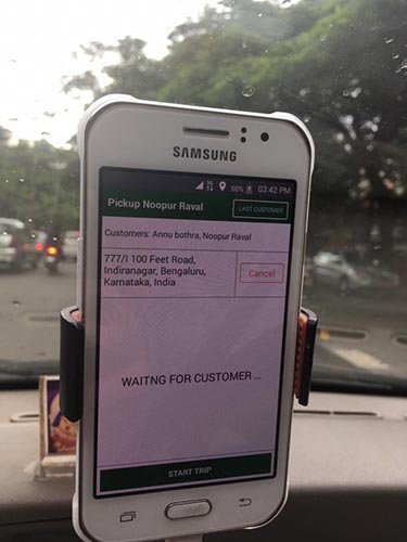 "A smartphone displays an Uber driver's pickup screen. The screen reads ""Waiting for customer"""
