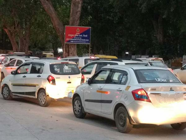A congested road full of white, ride-sharing cars
