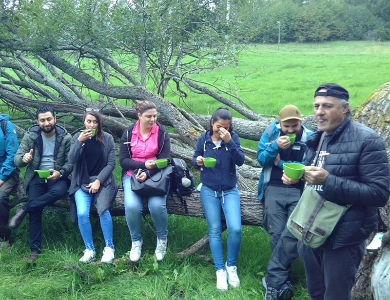 NBI participants sit on a large fallen log in a green field while taking their coffee break during an NBI.