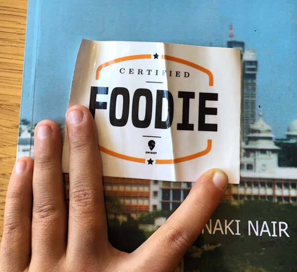 """A hand opens open a curled sticker reading """"Certified foodie"""""""