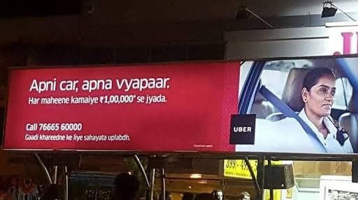 A photograph of a billboard. The left side is red with text. The right side is a photograph of a woman in a car. Between the two is the Uber logo.