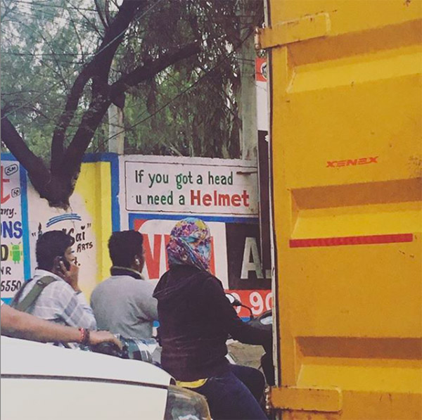 """Photographs of three riders without helmets with a sign behind them reading """"if you got a head u need a helmet""""."""