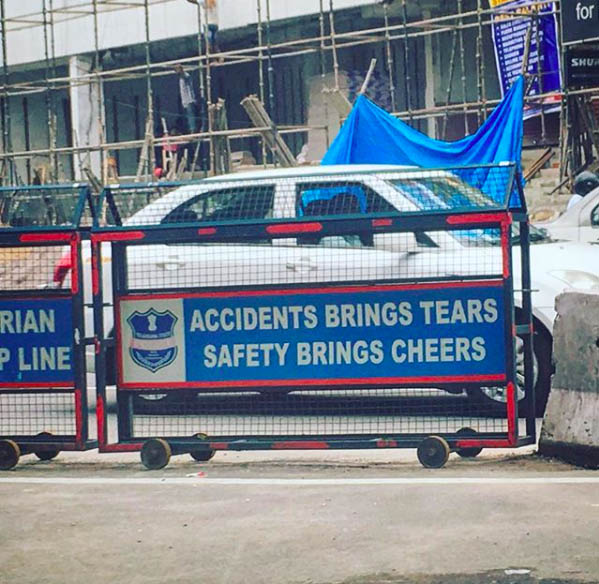 "Photograph of road dividers with signs that read ""Accidents brings tears. Safety brings cheers."""