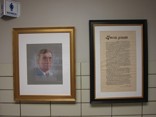 Photograph of a framed drawn portrait of a man. To the right of it is a framed page of calligraphy text titled Tom Jones.