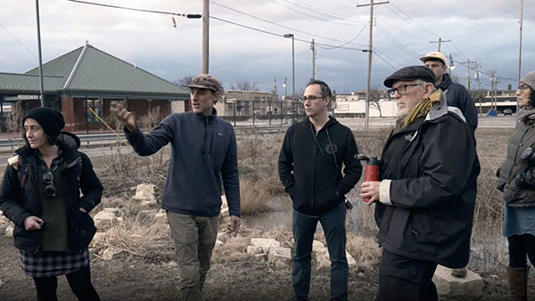The image shows artist Chris Carl in the middle of a group of four researchers. They are wearing winter jackets and standing on a brown grass field, with the industrial landscape of Granite City in the background. Chris Carl is gesturing with his hands, as he explains his project.