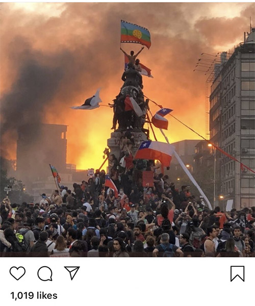 hundreds of protesters surround and climb an obelisk to plant the mapuche flag against and orange sunset