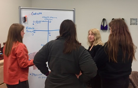 Four women standing around a whiteboard discussing.