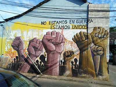 "A street mural shows fists rising from the ground, and a caption reading ""we're not at war, we're united."""