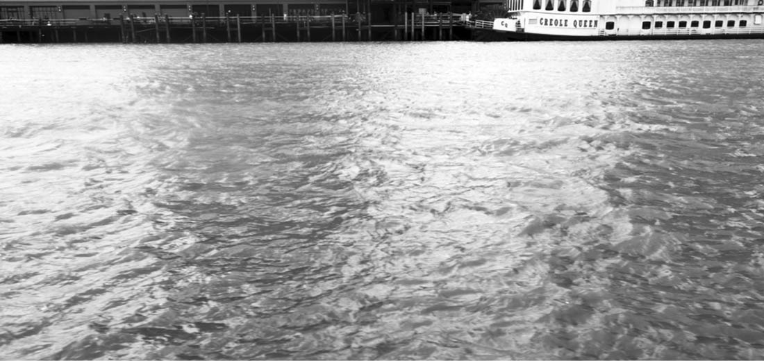 Black and white photograph of the Mississippi River, taken aboard a tourist replica of a steam boat, the Mississippi River Queen.