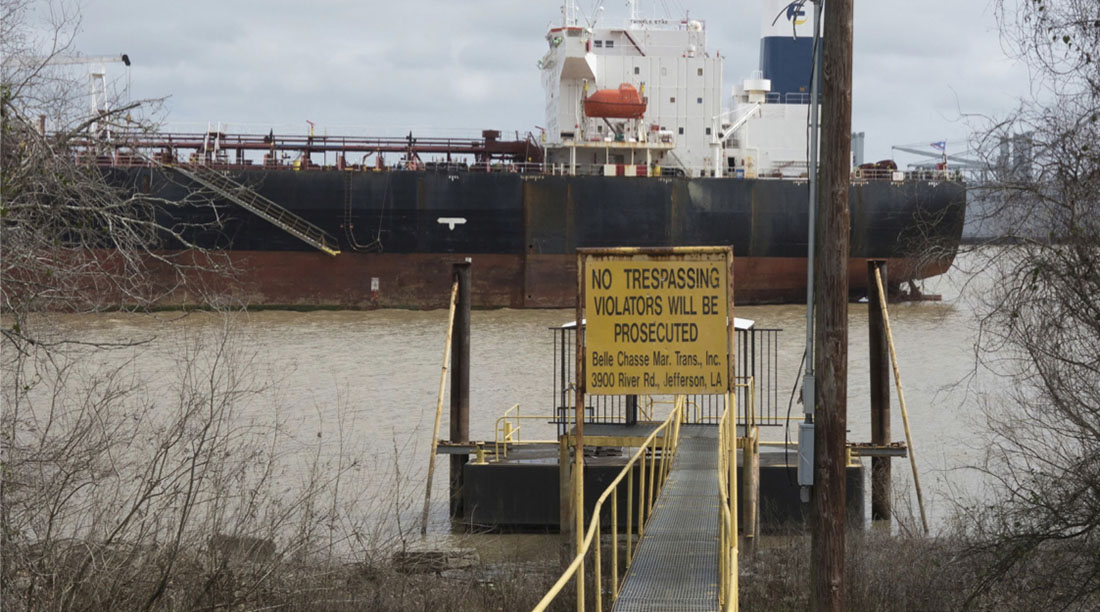 Photograph of a petrochemical tanker on the Mississippi River with industrial dock in foreground and a sign reading, 'No trespassing; violators will be prosecuted.  Belle Chasse Mar. Trans. Inc. 3900 River Rd, Jefferson, LA.'