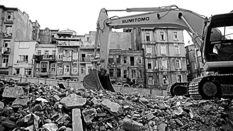 The black-and-white image of a bulldozer with in the midst of the rubble from house demolition. Houses at the background remind of the buildings on the previous image.