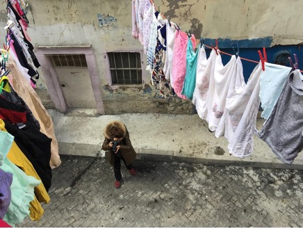 The image taken from the second floor showing a photographer standing under clothes lines with clean colorful laundry and taking a picture of something.