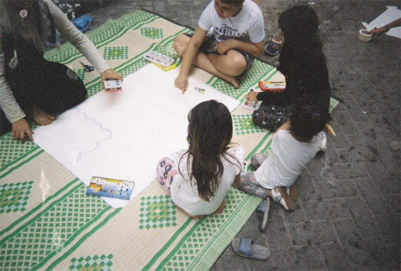The image shows five children sitting on a rug on a street and drawing with crayons.