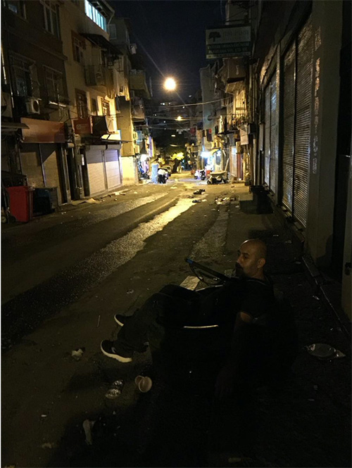 The image of a man sitting in the tire on the right side of a street. It is nighttime, the street is dark. A street light illuminates the street from afar.