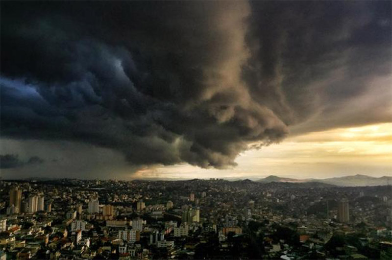 Dark, ominous storm clouds hover over a dense city with mountains in the background.