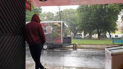 A man stands under an awning and watches the rain.