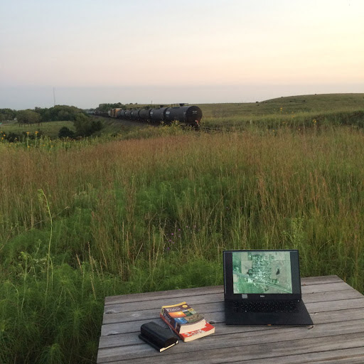 Color photograph of the 'right of way' zone near the BNSF railroad. Laptop and books on outdoor table in foreground, train moving on tracks in background.