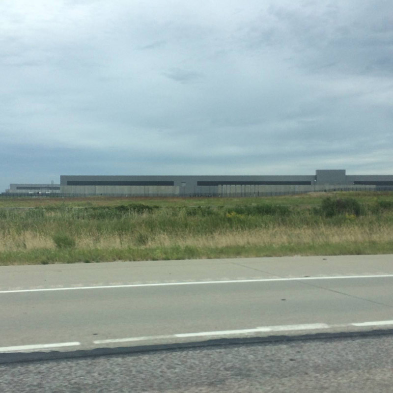 Exterior of a Facebook data center in Altoon, Iowa. Road and field in foreground.