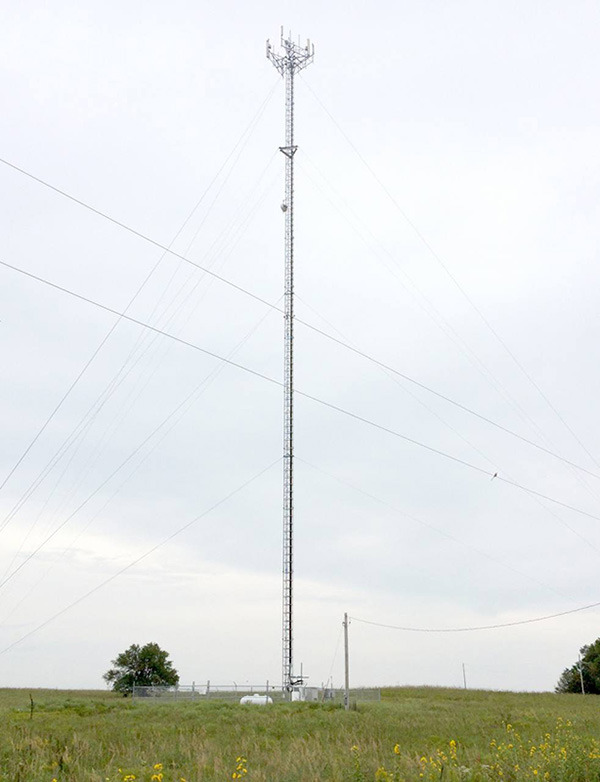 Color photo of a wireless internet cell tower behind the Bazaar Cemetery in the Flint Hills region of Chase County, Kansas.