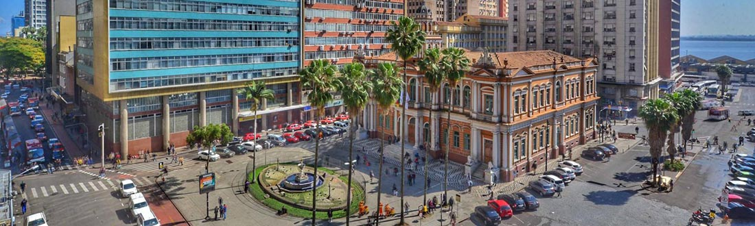 """Picture of """"Paço da Prefeitura"""" taken from above. It focuses on the city hall building, built in 1901, the square and the water fountain in front of it. There are tall buildings around it. People are walking on the streets and there are several cars parked. The Guaíba River is spotted on the horizon."""