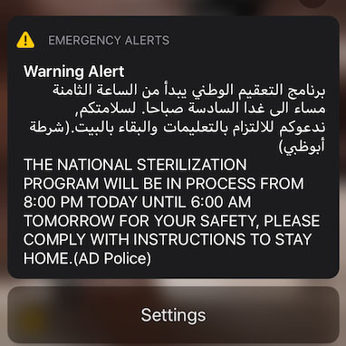 """An emergency alert on a cell phone screen in Arabic and English reading """"The national sertilization program will be in process from 8:00 PM today until 6:00 AM tomorrow for your safety, please comply with instructions to stay home. (AD Police)"""