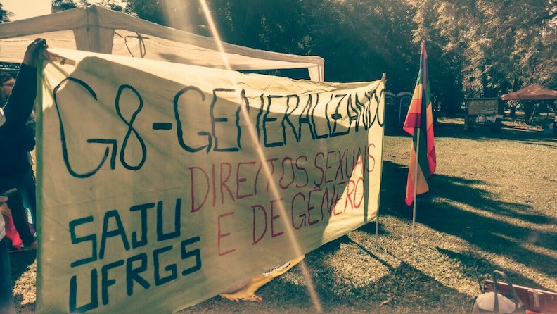 """At a sunny park, a large banner is held that says """"G-8 Generalizando"""" and """"sex and gender rights."""" A rainbow pride flag stands on a pole next to the banner."""