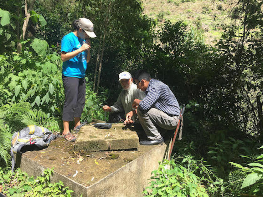 Three people huddled around a cement well in the middle of green foliage, using scientific equipment to measure dissolved oxygen