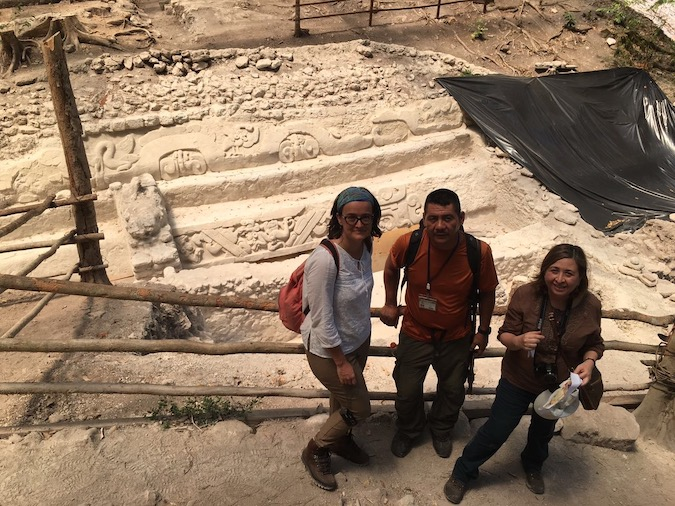 Three people standing in front of an archeological site, of murals etched into the ground or on the side of a Maya ruin