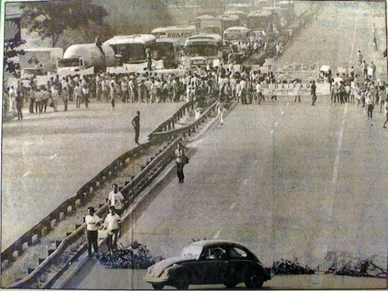 Black and white photo of protestors closing a road holding banners, with a line of vehicles behind them.