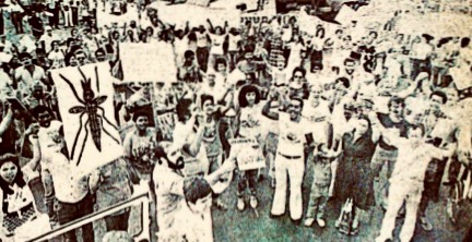 Black and white photo of protestors, some are holding signs and, most notably, one of them has a mosquito image.