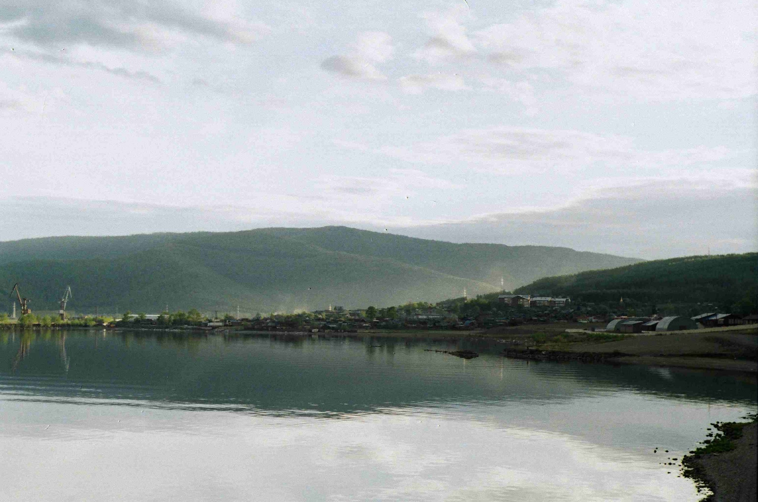 A landscape of the lake shore and the hills behind the lake shore. The water is still and reflects the hills. The sky is cloudy with some patches of blue.