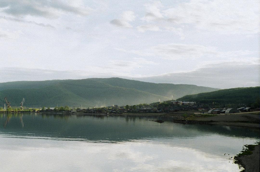 Пейзаж берегов озера, На небе небольшие облака, холмистые берега и спокойная вода озера.