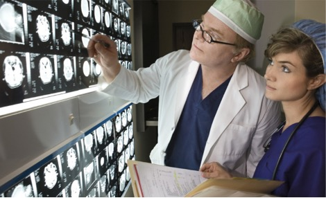 Photo of a male neurologist and a female nurse looking at neurodiagnostic brain scans. The nurse has astethoscope hanging down from her neck and a folder with documents in her hands. The doctor is pointing at a particular brain image, drawing the nurse's attention to it.