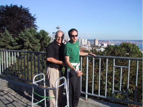 Photo of a father (on the left) and a son (on the right) standing by a metallic railing. It is a bright sunny day, with no cloud in the sky. Behind the railing, there are green trees and Seattle's cityscape. The son is wearing sunglasses, a green T-shirt, and dark trousers, with a grey hoody wrapped around his waist. The father is wearing a dark top and light trousers. The father is supporting his son from the back, the son is holding the railing with his left hand. Beside them is a walker.