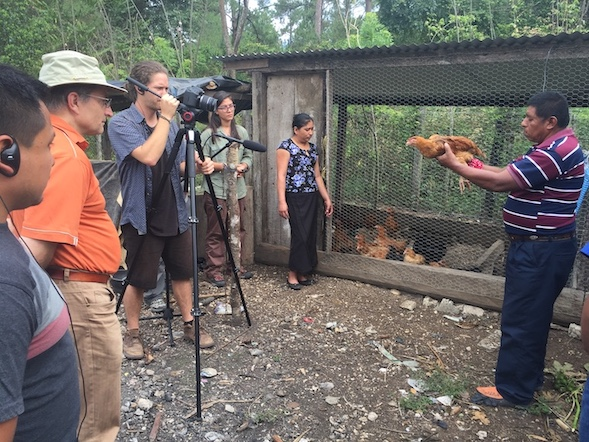 A Maya man is holding a chicken in front of a camera and looks to be explaining something. Behind the camera are a research team and film crew of five people. They are outdoors in a forested area.