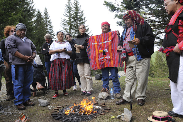 """Four Maya Elders standing around a small fire. One is holding a colorful red textile that reads, in Spanish, """"Great Confederation Ixim Ulew 2020."""" In the background are other research team members."""