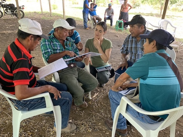 A group of people are sitting in plastic chairs over a flat dirt ground. Some have papers in their hand, they look to be discussing the project.