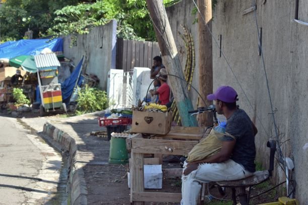 A Jamaican street with a few vendors sand a leaning telephone pole