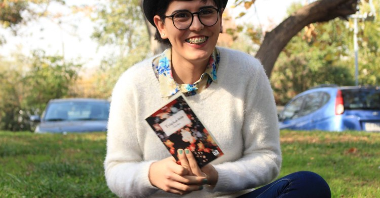 Mara Rita sits in a park holding her book, Tropico Mio. She is wearing a black bowler hat, dark rimmed glasses, a printed button down shirt, and a white sweater over it. She is simling.