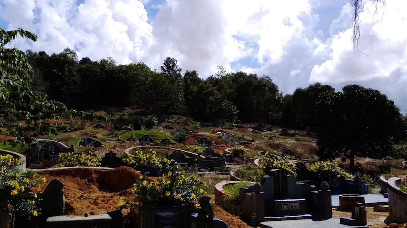 A landscape scene of cemetary on a small hill with a dozen or more headstones beneath a cloudy blue sky.