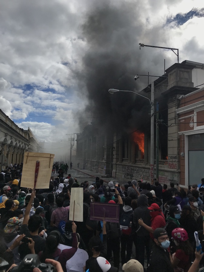 The photo looks over protestors in the street who are standing feet away from the Guatemala Congressional building. The building is on fire, and a smoke plume drifts off into the sky.