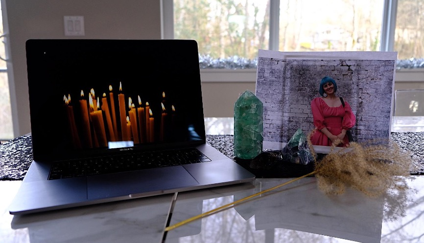 A photograph that shows a laptop and an altar on a counter. The laptop screen shows an image of burning candles. The altar includes a printed photo of the author who is a white woman with blue hair and in a pink dress standing in front of a brick wall. It also includes three crystals and a dried plant.