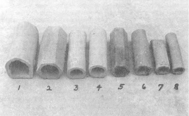 Eight segments of drainage pipes alongside one another. They differ in width and color.