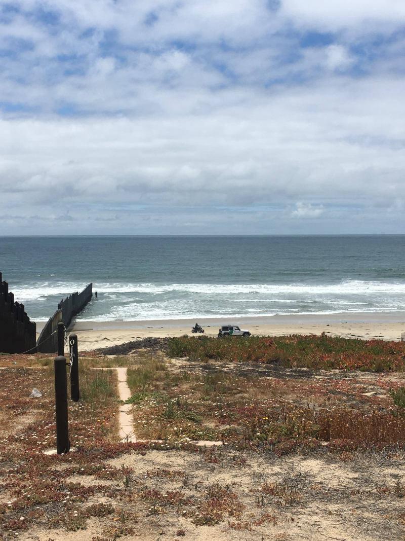 Muro fronterizo entrando en el Océano Pacífico.Océano y cielo nublado de fondo.Un jeep de la Patrulla Fronteriza y una motocicleta de la Patrulla Fronteriza vigilan el muro fronterizo.
