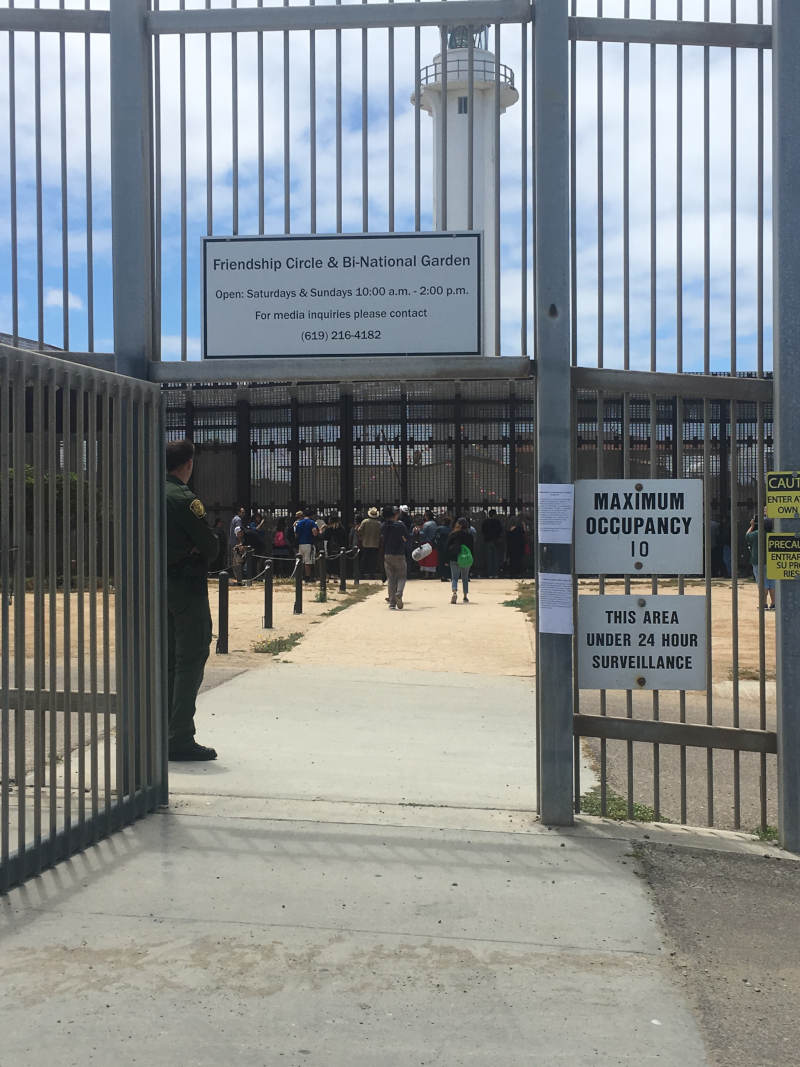 Gate opening in silver border fence with Border Patrol agent standing guard.