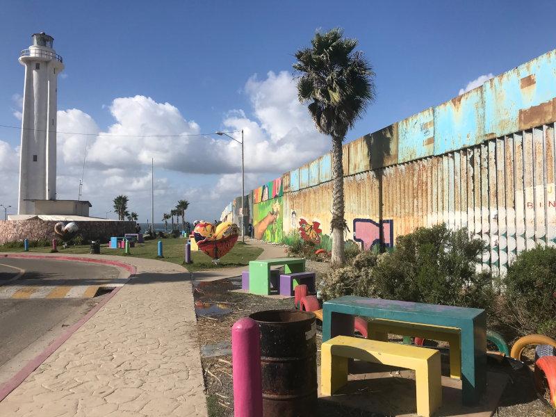 Parque con bancos multicolores y cerca fronteriza y jardín binacional a la derecha. El muro fronterizo tiene un mural brillante de una mano extendida en la distancia.