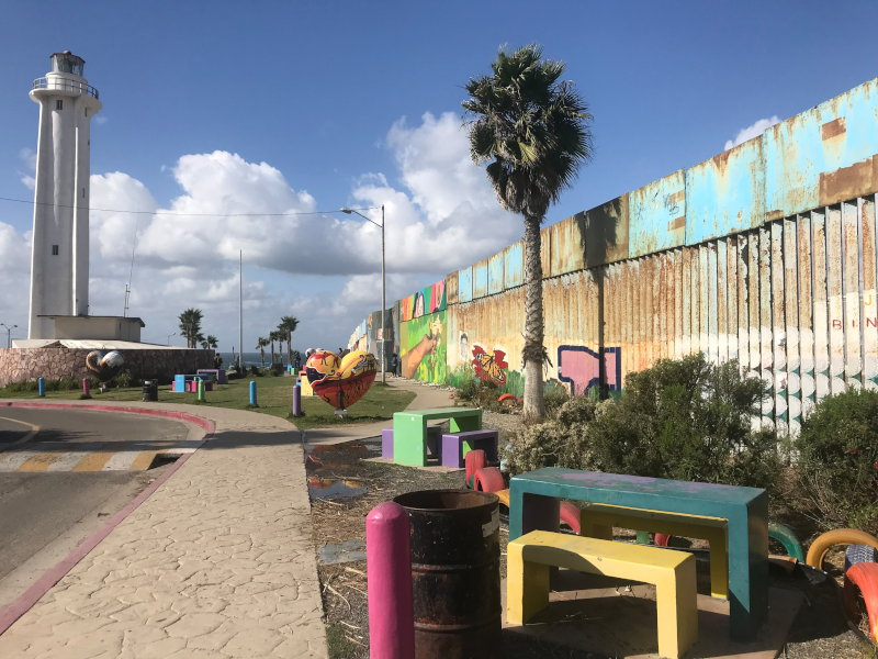 Park with multi-colored benches and border fence and binational garden to the right.
