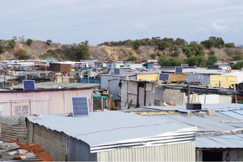 Roofs of informal settlement houses with small rectangular solar panels installed on them.