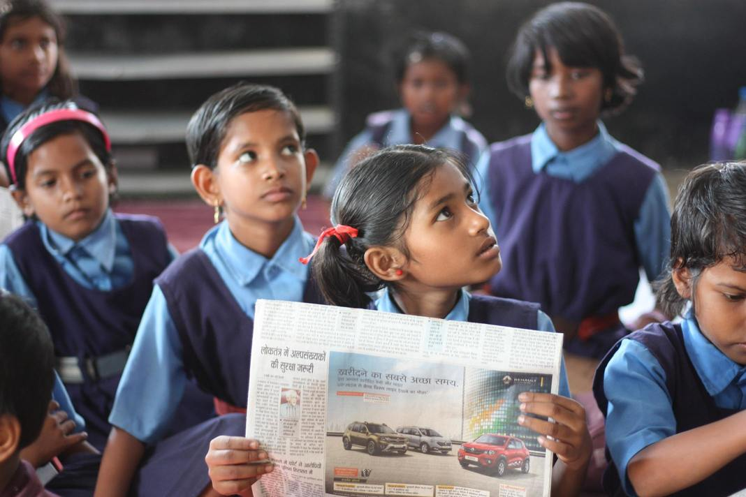 Pictured some female school students, seemingly in Indian public school uniform, in blue colored clothes. The girl in front is holding up a paper and looking to her left.
