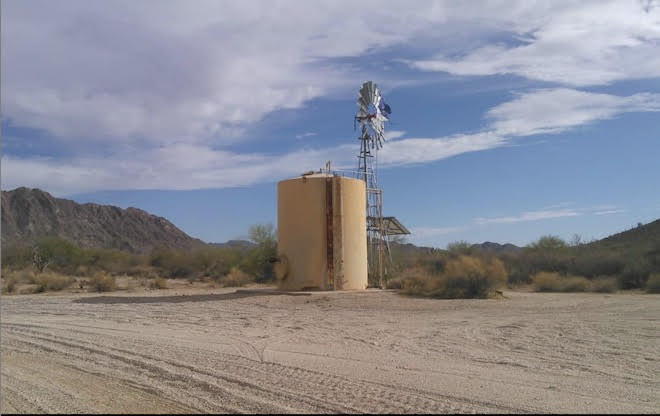 An Image of Papago Well, a large water tank with a faucet. Behind it there is a metal windmill, and barely visible is the purple humane borders flag marking this as a location containing potable water. The water tank sits in a desert landscape, near a sandy road marked by tire tracks.
